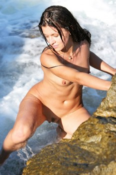 Naked babe swims in warm sea and lies in the sun