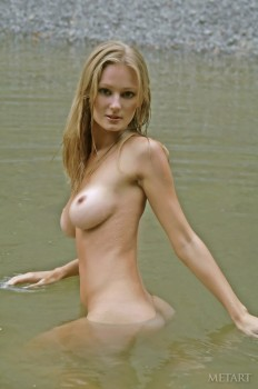 Sexy diva poses naked in the river.