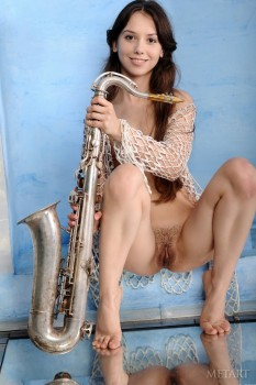 Stunning naked chick plays with a saxophone.