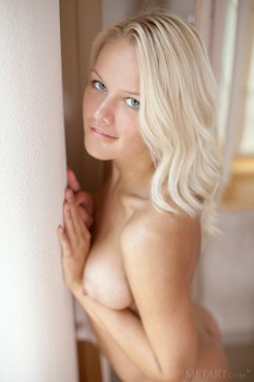 Naked blondie looks out of the window.