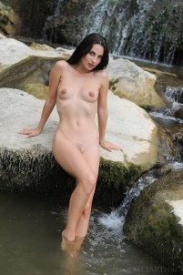 Slim brunette turns into a river nymph on the rock