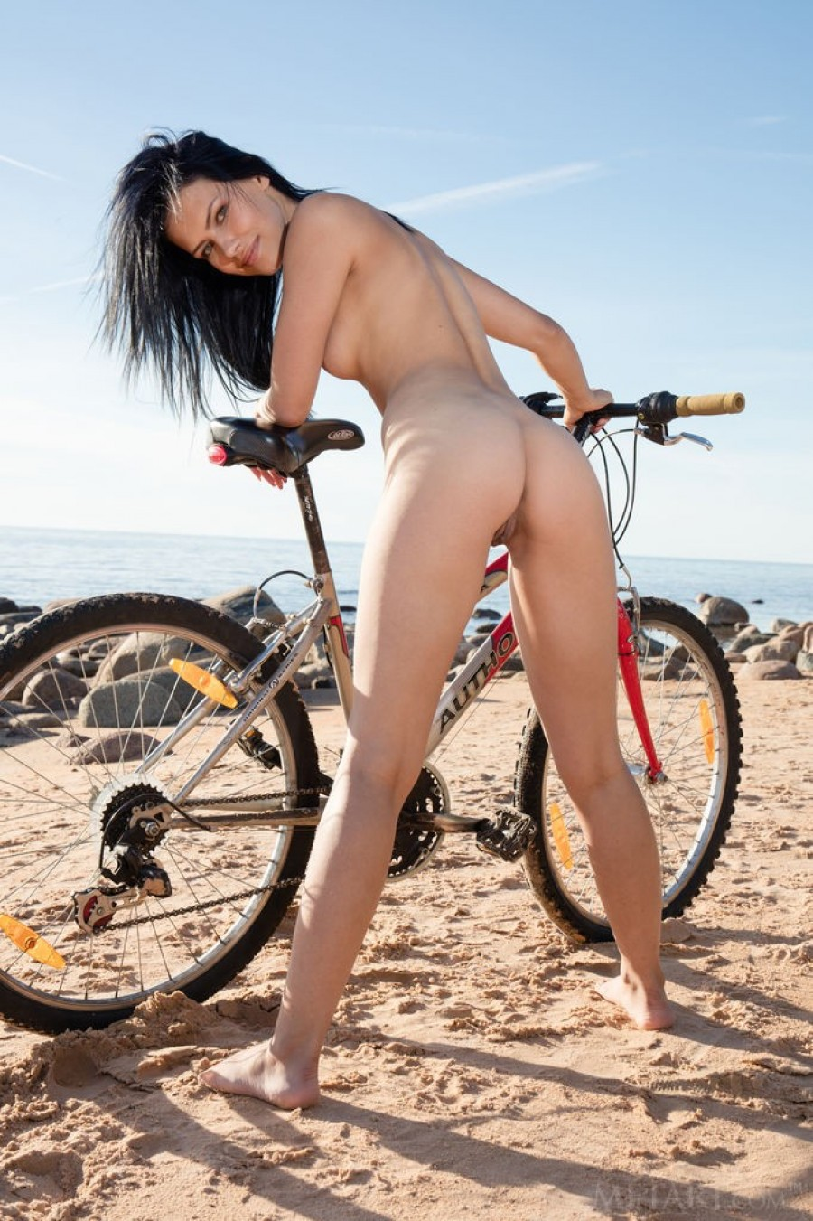 Brunette caresses wet pussy in the sand