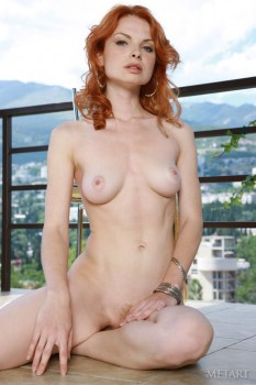 Sizzling hot redhead naked overlooking the city